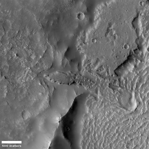 Flows and pitted material on the edge of Mars' great volcanic flood plain